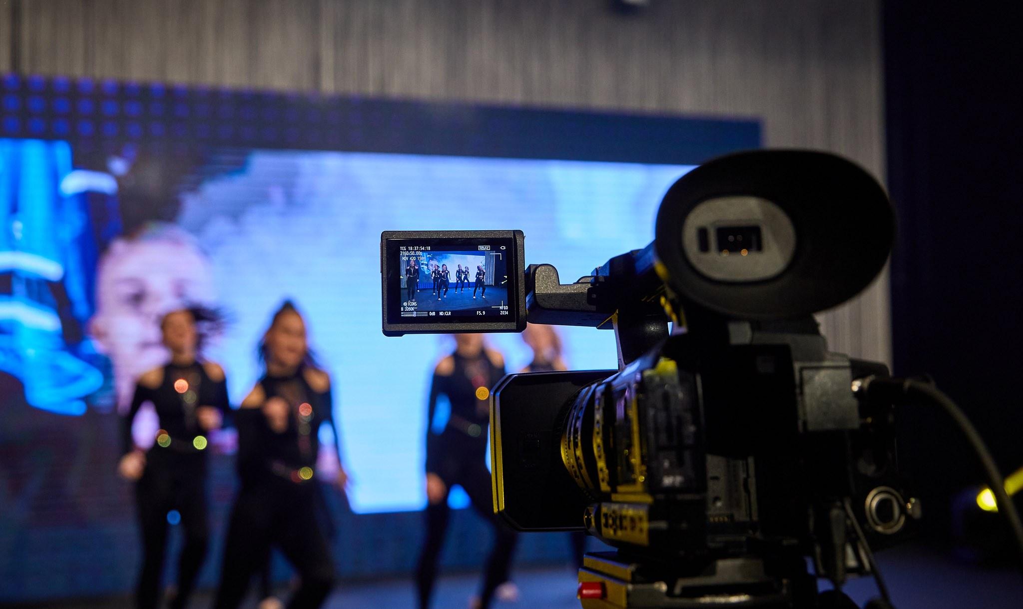 Kamera kuvaa tanssivia tyttöjä, joiden taustalla on led-screen.
